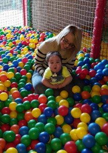 Max and his Mum in a colourful ball pit.