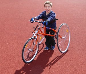 Child with three wheeled bike.