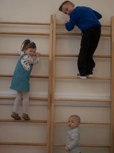 Three children climbing on an indoor gym climbing wall.