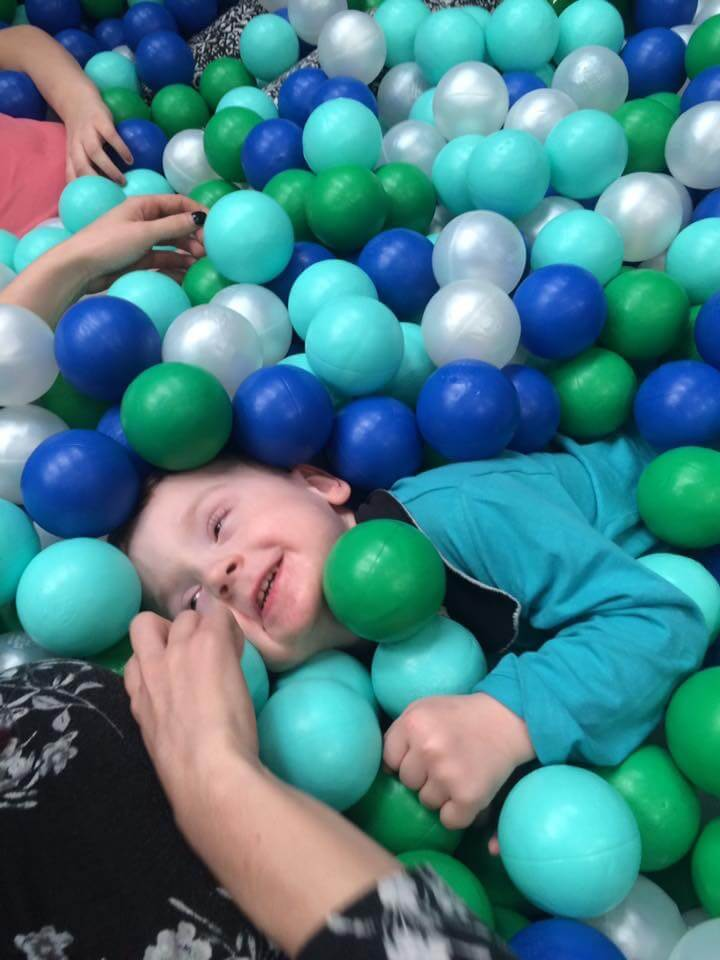 Child in a ball pit with blue and green balls.