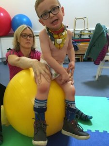 Sitting on a gym ball is a balance exercises for your child to try once they have completed the other exercises