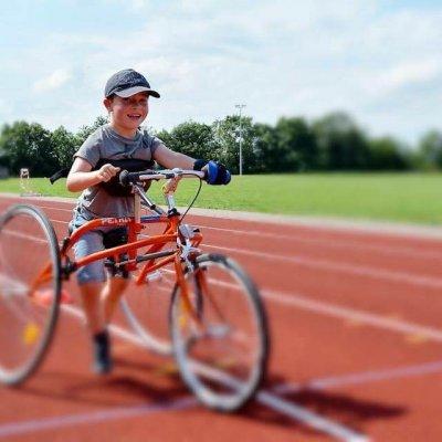 Child with three wheeled bike.